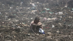 Young girl scavenges amidst filth of rubbish dump - stock footage