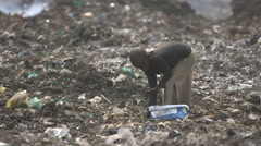 Young child scavenging on rubbish dump Stock Footage