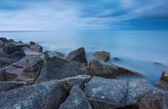 Beautiful Baltic sea landscape with stone breakwater. Tranquil long exposure  Stock Photos