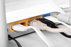 close up of internet wireless router with plugged cables - stock photo