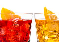 detail of red and yellow cocktail with orange slice on top isolated on white  - stock photo