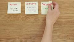 Woman's hand put post it papers with the days of the week, top view HD - stock footage