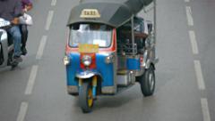 BANGKOK, THAILAND - CIRCA FEB 2015: Motor-Rickshaw Turning on a Busy Street i Stock Footage