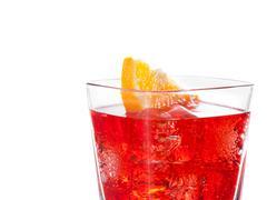 detail of red cocktail with orange slice isolated on white background - stock photo