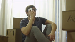 Man is Talking on Phone in New House after Moving - stock footage