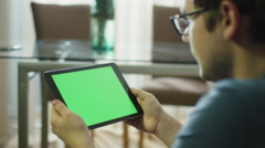Man is Holding Tablet with Green Screen in Landscape Mode at Home - stock footage