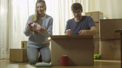 Couple is Unpacking Cardboard Boxes after Moving to New Flat. - stock footage