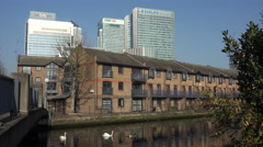 Row of terraced houses, Canary Wharf skyscrapers, London, England Stock Footage