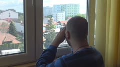 Behind home windows young man look through binoculars spying, stalking, rude boy - stock footage
