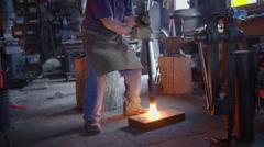 Blacksmith creates sparks while pounding metal on floor HD Stock Footage