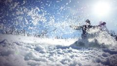 Young man snowboarding on mountains at sun and knocked the snow At the camera Stock Footage