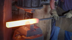 Blacksmith uses industrial hammer to shape hot steel bar HD Stock Footage