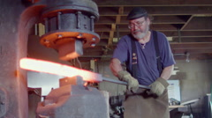 Slow motion blacksmith working hot steel rod with powered hammer HD - stock footage