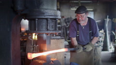 Blacksmith working hot steel with industrial hammer HD Stock Footage