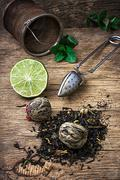 tea brew with lime and mint on wooden background - stock photo