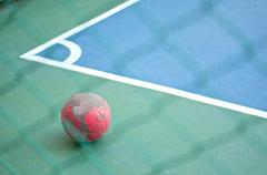 Old red ball at corner in futsal field - stock photo