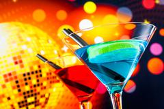 Red and blue cocktail with sparkling disco ball background with space for tex Stock Photos