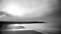 Time-lapse scenery of a bay in evening during the tide in black and white - stock footage