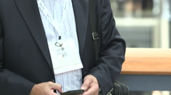 Man at trade show types on mobile phone Stock Footage