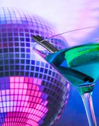Stock Photo of blue cocktail with sparkling disco ball background with space for text