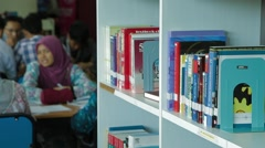 Track and Pan Shot of Books on Shelf and Students Studying in Library in Penang Stock Footage