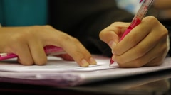 Close Up Shot of A Hand Holding A Red Pen and Writing Lecture Notes Stock Footage