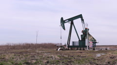 Pump oil jack working in agriculture field Stock Footage