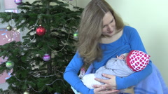 Mother mom breast feed infant baby near Christmas tree Stock Footage