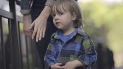 Little Boy Looks Worried, Mother Takes His Hand In Hers And They Walk Together Stock Footage