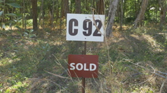 Sold sign in front of plot of land. Closeup. Costa Rica. Stock Footage