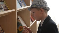 Schoolboy reading a book in the library Stock Footage
