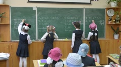 The girls at the blackboard in the classroom mathematics solved the problem and  Stock Footage