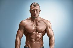 Attractive male body builder on blue background - stock photo