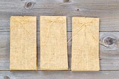 Three new burlap bags on aged wood Stock Photos