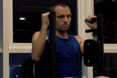 Young man exercising on machine in gym at night, taking break and drinking  NTSC Stock Footage