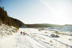 Caucasian family cross-country skiing in snowy field Stock Photos