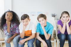 Bored children resting chins in hands Stock Photos