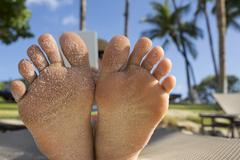 Close up of bottom of sandy feet of Caucasian woman Stock Photos