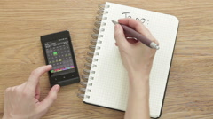 """Woman planning """"To do"""" list with smartphone calendar and notepad, top view HD Stock Footage"""