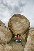 Hispanic woman lifting boulder on rocky hillside Stock Photos