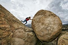 Hispanic woman pushing boulder on rocky hillside Stock Photos