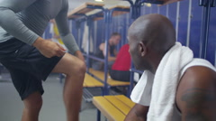 4K Sports players or gym buddies chatting together in men's locker room - stock footage