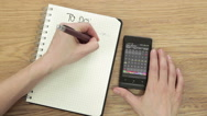 """Stock Video Footage of Woman planning """"To do"""" list with smartphone calendar and notepad, time lapse HD"""