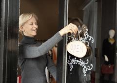 Caucasian small business owner hanging open sign on front door Kuvituskuvat