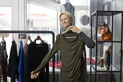 Older Caucasian woman shopping in clothing store Stock Photos