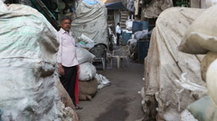 Portrait of local man in street with sacks and stored products in Mumbai. Stock Footage