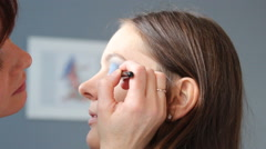Makeup artist applying black eye liner to model eye. Full HD Stock Footage