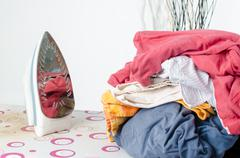 Pile of laundry and iron on ironing board Stock Photos