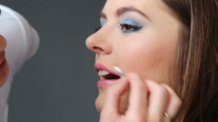 Makeup artist applying lip gloss to model lips, full HD - stock footage