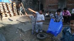 Kids playing with improvised balloon at street in Mumbai. Stock Footage